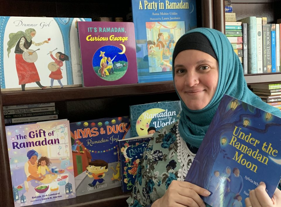 a woman stands in front of a bookshelf featuring picture books about Ramadan